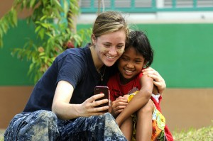 A Sailor takes a photo with a Thai girl during a community service event at The Child Development and Protection Center in Huay Yai, Thailand.